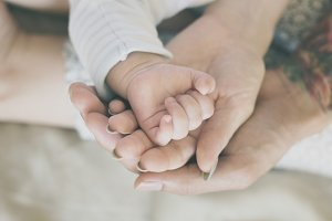 Close up of parents and baby's hands