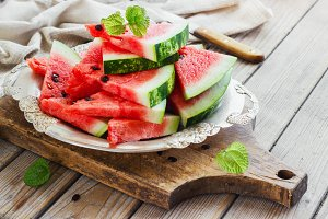 Fresh sliced watermelon in a metal bowl wooden background