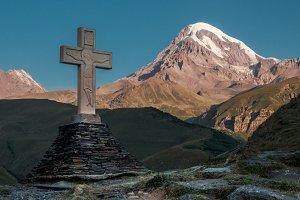 Cross in Kazbegi with view of mountain Kazbek