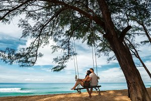 Couple in love on a swing by the sea