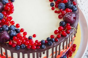 Bright festive cake with berries and chocolate on a white wooden background