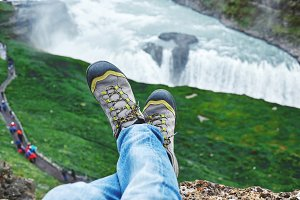 man's feet in boots on the waterfall background in Iceland