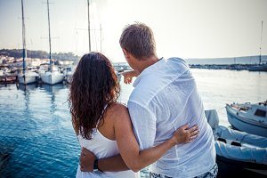 Back view, couple hug on boat marine background