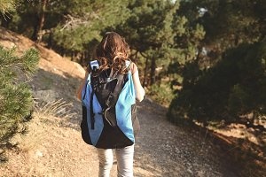 Woman hiker standing outside in forest with backpack