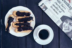 Coffee and eclairs on a wooden table
