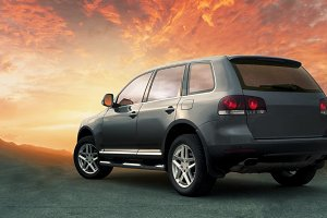 crossover SUV in the hillside with sunset in the background.