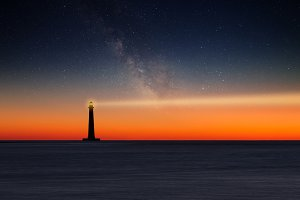 Lighthouse under starry sky