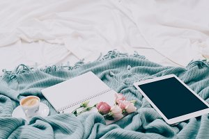 Toned Flat lay tablet, phone, cup of coffee and flowers on white blanket with turquoise plaid
