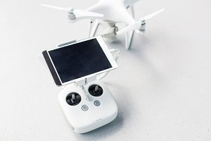 Drone with a remote control and a tablet on it on a gray concrete background. Quadcopter with camera ready to shoot video