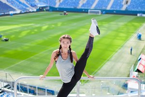 Young sporty girl jumped high and spread her legs in different directions on the background of a football stadium. Woman in sportswear a great stretch