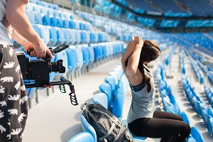The videographer shoots on a professional camera like a sporty girl warming up, sitting in the stadium