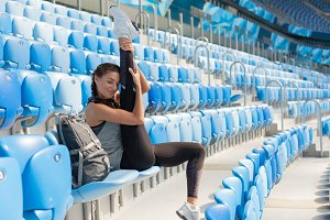 Sporty young girl with tanned skin makes stretch sitting on the seat in the stadium. The woman pulls the leg up, making the warm-up