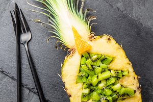 Holidey diet concept or tropical Christmas menu concept. Christmas tree made from pineapple and kiwi on slate board. Ideas for Christmas New Year menu