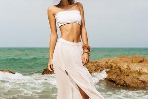 Beautiful woman walk at stone beach.