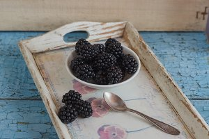 Blackberry in the white bowl with a spoon on the wooden tray