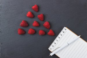 Red raspberries, notebook and a pen on the black slate stone background