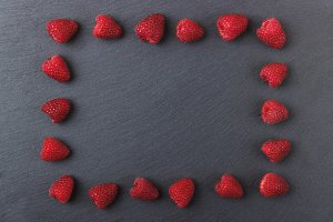 Frame from red raspberries on the black slate stone background