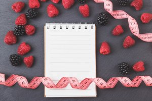 Red raspberries, blackberry, tape measure and notebook on the black slate stone background