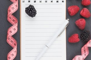 Red raspberries, blackberry, tape measure, notebook and a pen on the black slate stone background