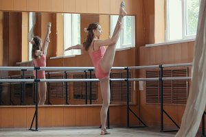Girl Ballet Dancer Training in mirror room - pink suit