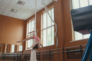 Young acrobatic girl shows the flexibility of the body at the ballet bar