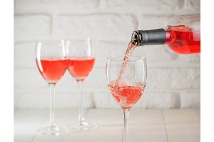 Pouring pink wine from bottle into wineglass