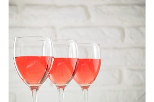 Three wineglass with pink wine on white brick wall background