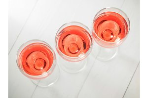 Three wineglass with pink wine on white wooden table