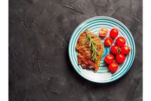 Fried steak and vegetables on blue plate, copy space