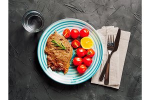 top view of fried steak and vegetables in blue plate