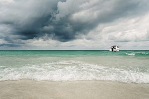 Exotic beautiful marine beach  with boat on blue water and stormy clouds sky