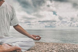 Man meditating on a high cliff above the sea in the Lotus position