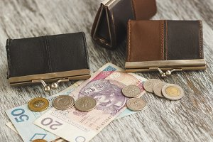 Polish zloty with little wallets on the old wooden background