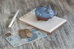 Polish zloty, notebook and piggy bank on the wooden background