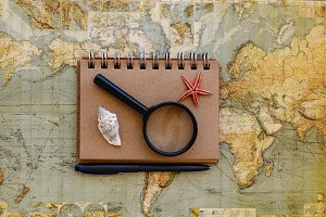 Travel flat lay with notepad magnifying glass and seashells plac