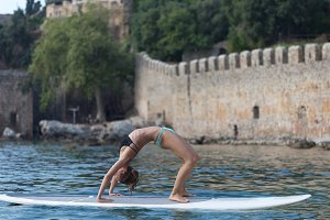 Fit woman backbending on stand up paddle