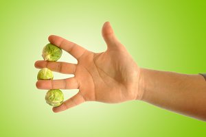 hand grabbing three brussels sprouts