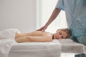 Attractive young woman receiving massage at spa. Relaxation treatment for shoulders, close up