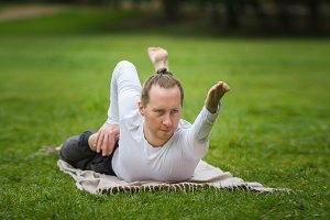 A man - yoga instructor performs flexibility exercises in park