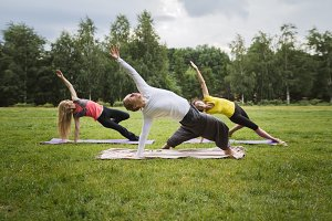 Training in park - instructor shows flexibility exercise for group of girls in park