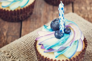 Festive cupcake on a wooden background with bright cream and blueberry with a candle rustic style