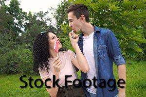 Teenage couple eating a lollipop