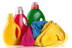 bottle laundry detergent and conditioner with towels isolated on white background