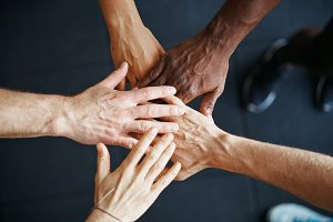 Diverse people standing with their hands together in a gym