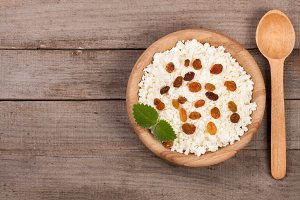 Cottage cheese with raisins in a wooden bowl on old wooden background with copy space for your text. Top view