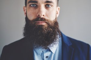 Focused young entrepreneur with a long beard wearing a blazer