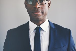 Focused young African executive wearing a suit and glasses