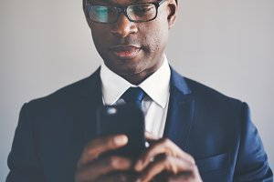Focused young African businessman reading messages on a cellphone