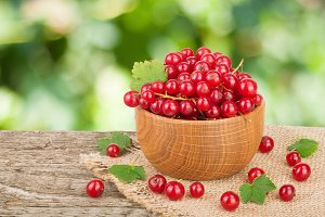 Red currant berries in wooden bowl on wooden table with blurry garden background