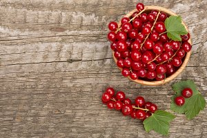 Red currant berries in a wooden bowl with leaf on the old wooden background with copy space for your text. Top view